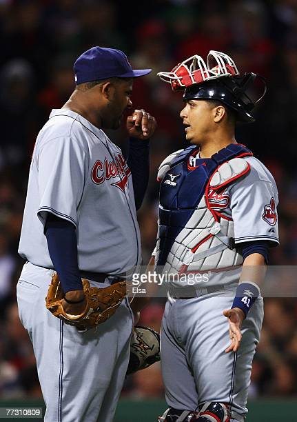Starting pitcher CC Sabathia of the Cleveland Indians talks with catcher Victor Martinez in the third inning of Game One of the American League...