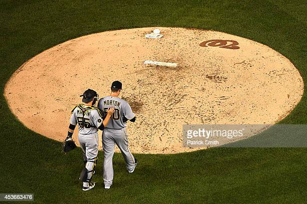 Starting pitcher Charlie Morton of the Pittsburgh Pirates is talked to by catcher Russell Martin of the Pittsburgh Pirates as he walks back to the...