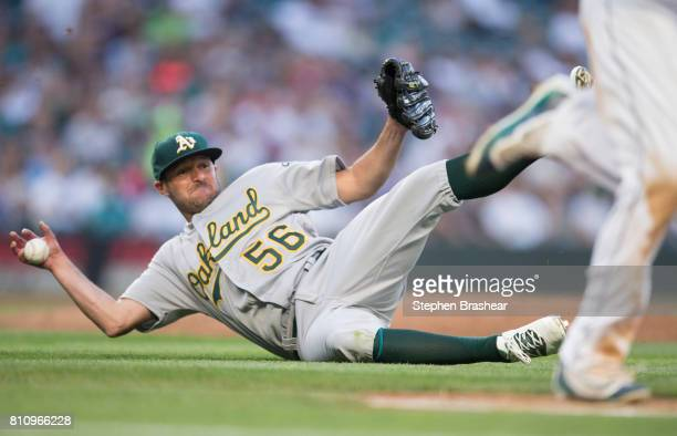 Starting pitcher Chris Smith of the Oakland Athletics slides to the ground as he tries to get to a ball hit by Danny Valencia of the Seattle Mariners...