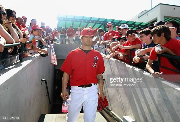 Starting pitcher C.J. Wilson of the Los Angeles Angels of Anaheim walks out onto the field past fans before the spring training game against the San...