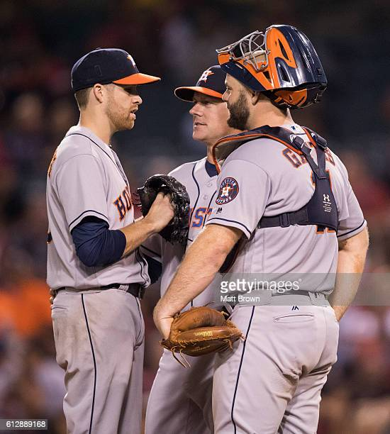 Starting pitcher Collin McHugh manager AJ Hinch and catcher Evan Gattis of the Houston Astros talk as Hinch makes a visit to the mound for a pitching...