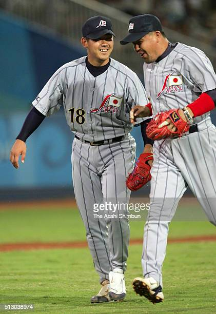 Starting pitcher Daisuke Matsuzaka of Japan walks toward the dugout with Norihiro Nakamura during the Baseball Preliminary match between Japan and...