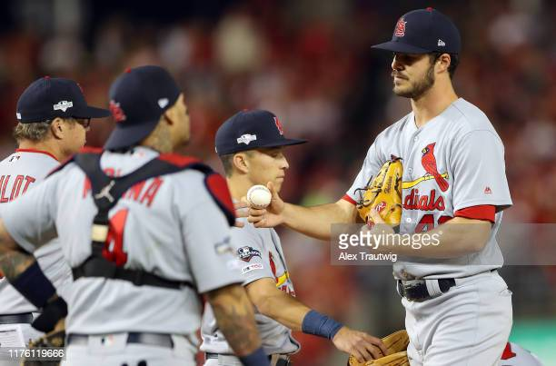 Starting pitcher Dakota Hudson of the St Louis Cardinals hands the ball to manager Mike Shildt in the bottom of the first inning of Game 4 of the...