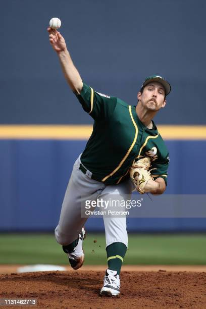 Starting pitcher Daniel Mengden of the Oakland Athletics throws a warmup pitch during the first inning of the MLB spring training game against the...
