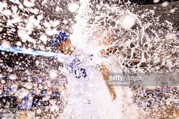 Starting pitcher Eric Skoglund of the Kansas City Royals gets dunked with water by Salvador Perez after making his major league debut against the...