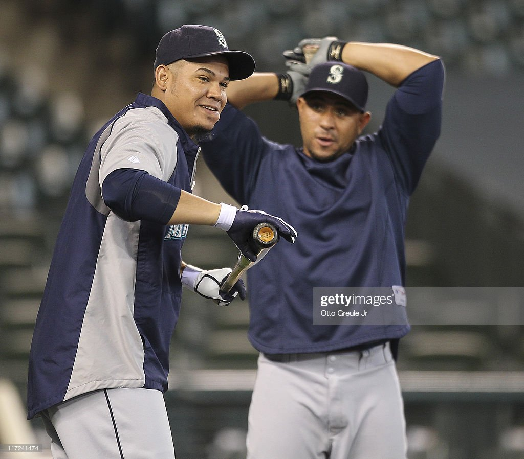 Starting pitcher Felix Hernandez #34 (L) and catcher Miguel Olivo #30 of the Seattle Mariners get ready to take batting practice prior to the game against the Florida Marlins at Safeco Field on June 24, 2011 in Seattle, Washington.