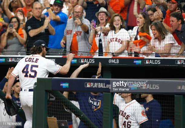 Starting pitcher Gerrit Cole of the Houston Astros high fives his teammates as the crowd cheers after he leaves the game in the eighth inning of Game...