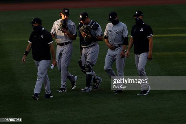 Starting pitcher Gerrit Cole of the New York Yankees and catcher Gary Sanchez walk in from the bullpen before the start of their game against the...