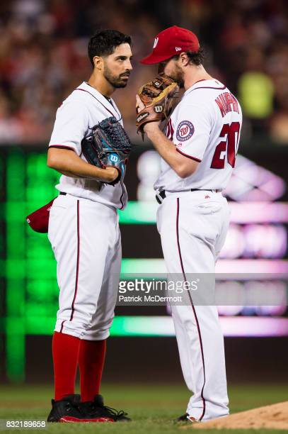 Starting pitcher Gio Gonzalez of the Washington Nationals talks with Daniel Murphy after giving up a single to Cameron Maybin of the Los Angeles...