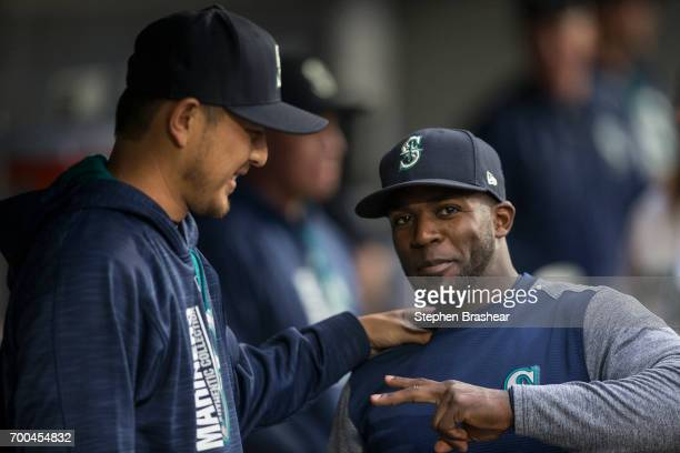 Starting pitcher Hisashi Iwakuma left and Guillermo Heredia of the Seattle Mariners joke around in the dugout before a game against the Detroit...
