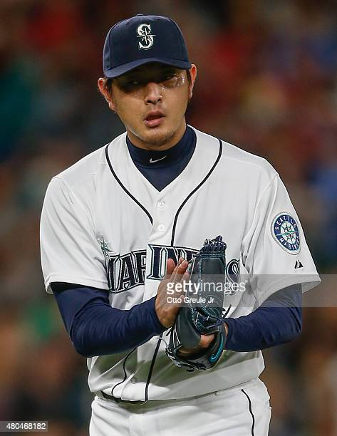 Starting pitcher Hisashi Iwakuma of the Seattle Mariners heads to the dugout after completing eight innings against the Los Angeles Angels of Anaheim...