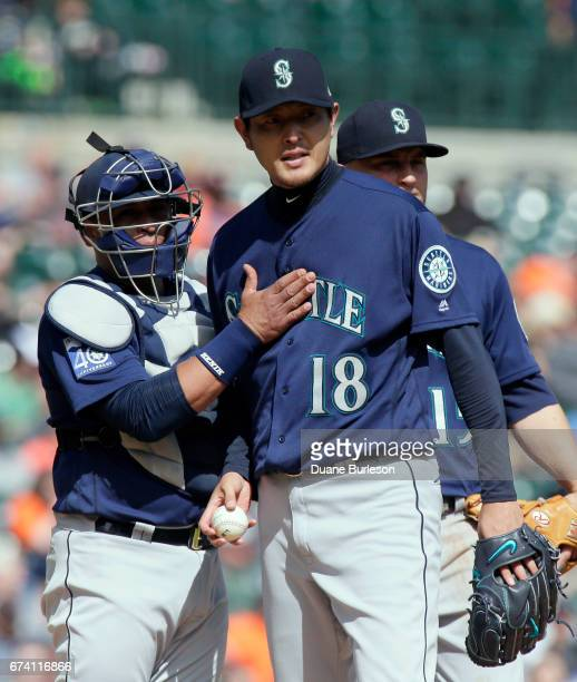 Starting pitcher Hisashi Iwakuma of the Seattle Mariners is congratulated by catcher Carlos Ruiz of the Seattle Mariners before leaving the game...