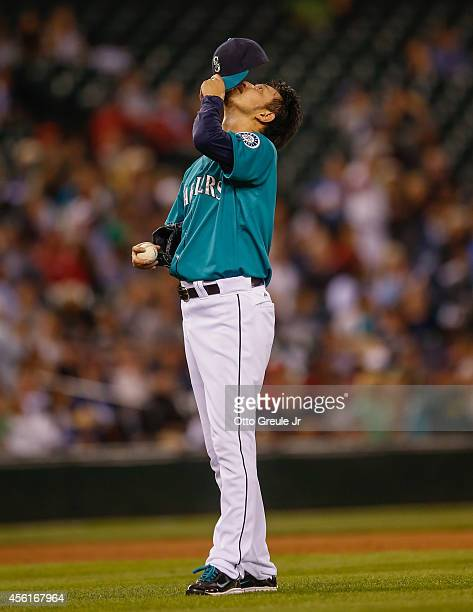 Starting pitcher Hisashi Iwakuma of the Seattle Mariners pauses on the mound after giving up a solo home run to Mike Trout of the Los Angeles Angels...