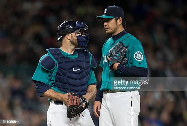 Starting pitcher Hisashi Iwakuma, right, of the Seattle Mariners talks with catcher Chris Iannetta of the Seattle Mariners on the pitcher's mound...