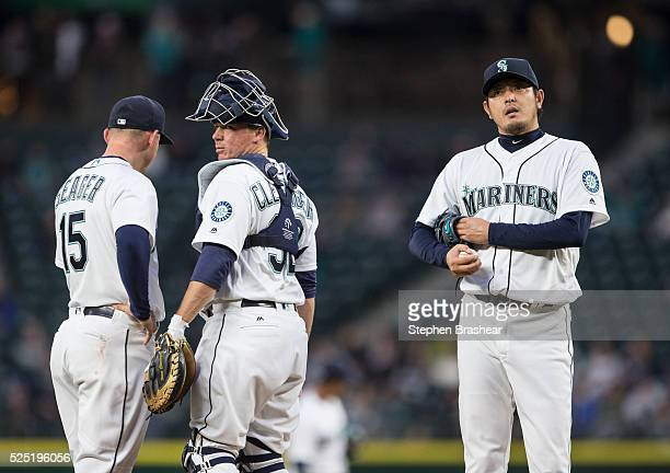 Starting pitcher Hisashi Iwakuma right of the Seattle Mariners third baseman Kyle Seager left of the Seattle Mariners and catcher Steve Clevenger of...