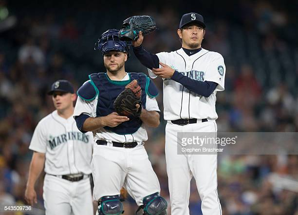 Starting pitcher Hisashi Iwakuma, right, of the Seattle Mariners waits with teammates catcher Chris Iannetta, center, and third baseman Kyle Seager...