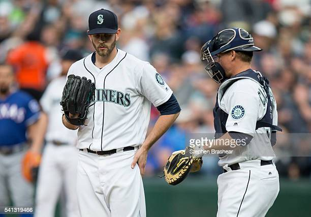 Starting pitcher James Paxton left of the Seattle Mariners meets at the pitcher's mound with catcher Steve Clevenger during a game against the Texas...