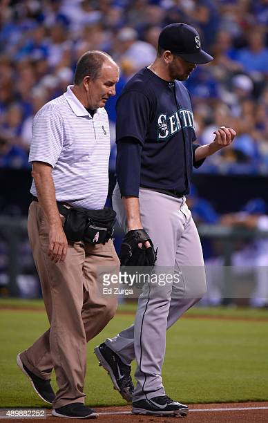 Starting pitcher James Paxton of the Seattle Mariners walks off the field with a team trainer in the second inning against the Kansas City Royals at...