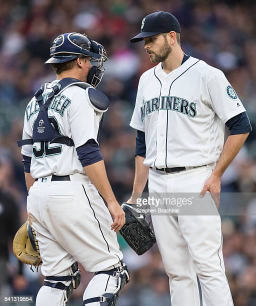 Starting pitcher James Paxton right of the Seattle Mariners meets at the pitcher's mound with catcher Steve Clevenger of the Seattle Mariners during...