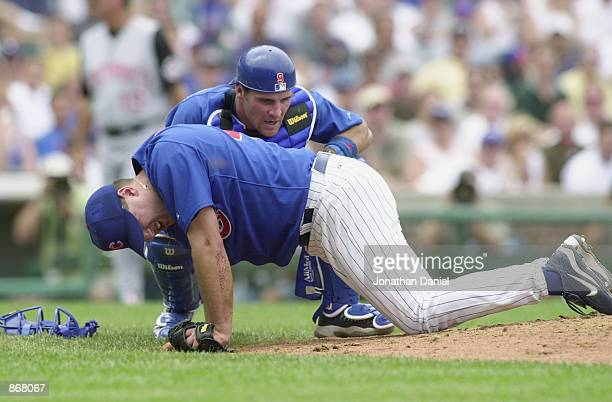 Starting pitcher Jason Bere of the Chicago Cubs writhes in pain after being hit on the knee by a line drive from first baseman Sean Casey of the...
