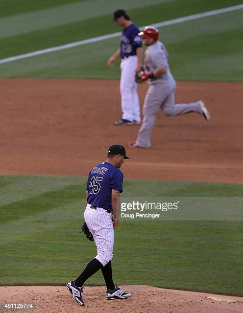 Starting pitcher Jhoulys Chacin of the Colorado Rockies returns the the mound as Matt Adams of the St. Louis Cardinals rounds the bases on his solo...