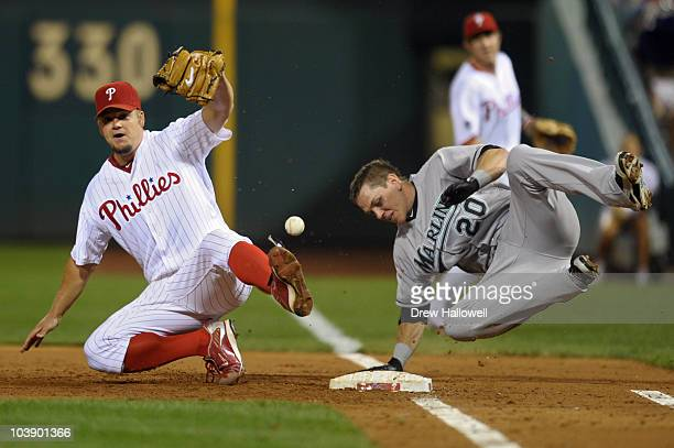 Starting pitcher Joe Blanton of the Philadelphia Phillies drops the ball after a collision at first base with Logan Morrison of the Florida Marlins...