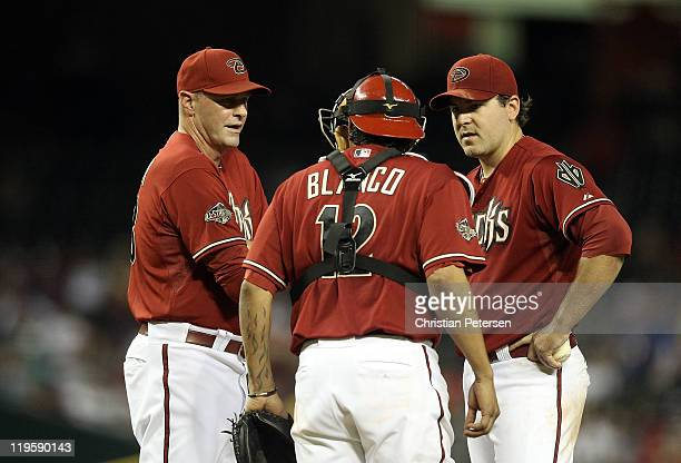 Starting pitcher Joe Saunders of the Arizona Diamondbacks talks with manager Kirk Gibson and catcher Miguel Montero during the Major League Baseball...