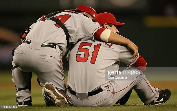 Starting pitcher Joe Saunders of the Los Angeles Angels of Anaheim gets a hug from catcher Mike Napoli after diving for a ball and landing hard...
