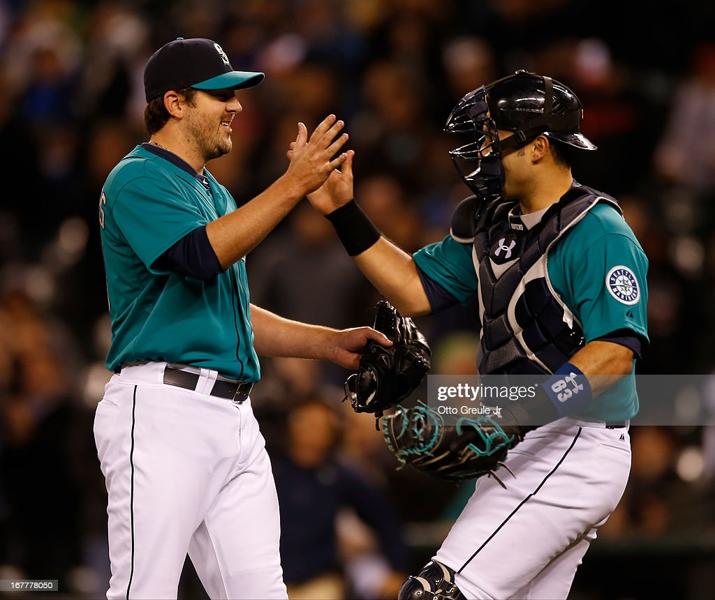 Starting pitcher Joe Saunders #23 (L) of the Seattle Mariners celebrates with catcher Jesus Montero #63 after defeating the Baltimore Orioles 6-2 at Safeco Field on April 29, 2013 in Seattle, Washington.