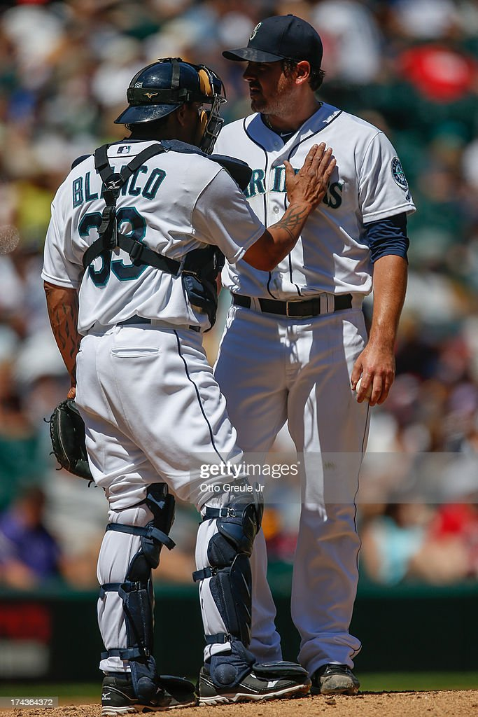 Starting pitcher Joe Saunders #23 of the Seattle Mariners gets a visit from catcher Henry Blanco #33 after giving up an RBI double to Carlos Santana of the Cleveland Indians in the first inning at Safeco Field on July 24, 2013 in Seattle, Washington. Cleveland defeated the Mariners 10-1.