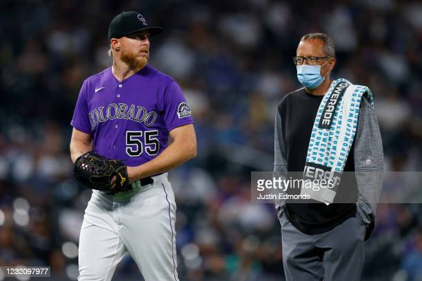 Starting pitcher Jon Gray of the Colorado Rockies exits the game alongside a member of the training staff during the sixth inning of the MLB game...
