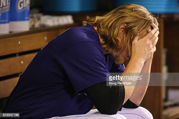 Starting pitcher Jon Gray of the Colorado Rockies sits on the dugout bench after being removed from the game against the Los Angeles Dodgers after...