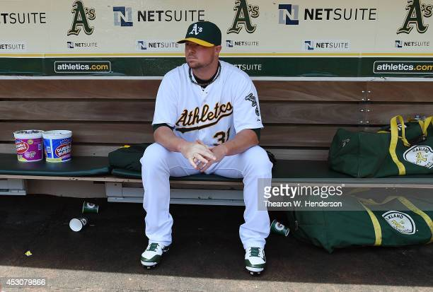 Starting pitcher Jon Lester of the Oakland Athletics sits and looks on from the dugout prior to warming up for his start against the Kansas City...