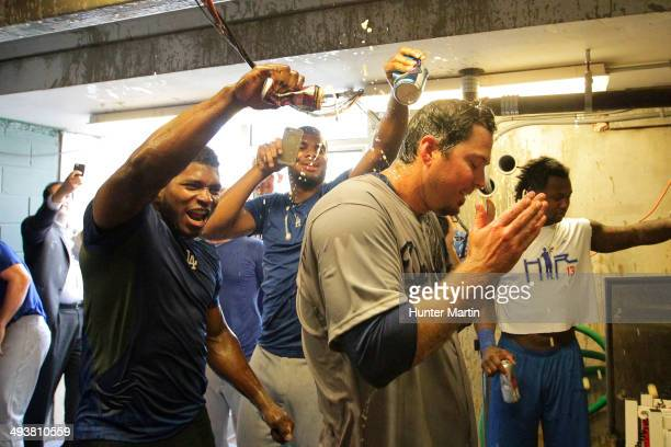 Starting pitcher Josh Beckett of the Los Angeles Dodgers is sprayed by teammates Yasiel Puig and Kenley Jansen outside of the clubhouse after...
