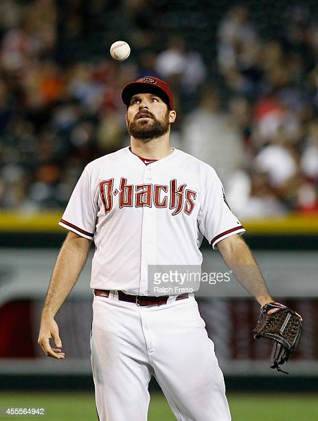 Starting pitcher Josh Collmenter of the Arizona Diamondbacks reacts by tossing the ball in the air after giving up a hit to Hunter Pence of the San...