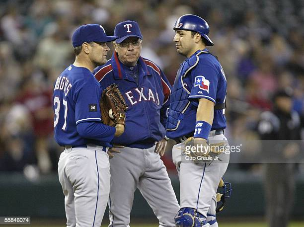 Starting Pitcher Kenny Rogers of the Texas Rangers talks with bullpen coach Mark Conner and catcher Rod Barajas during the game against the Seattle...