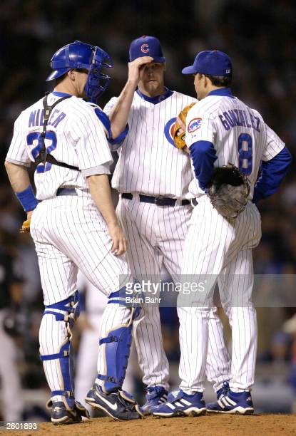 Starting pitcher Kerry Wood of the Chicago Cubs confers with teammates Damian Miller and Alex Gonzalez in the fifth inning against the Florida...