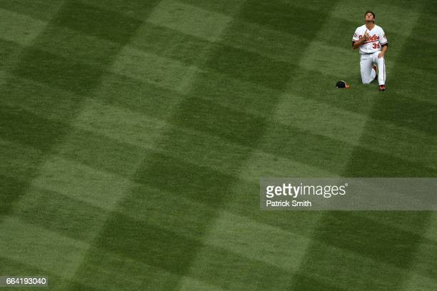Starting pitcher Kevin Gausman of the Baltimore Orioles prays before playing the Toronto Blue Jays during their Opening Day game at Oriole Park at...
