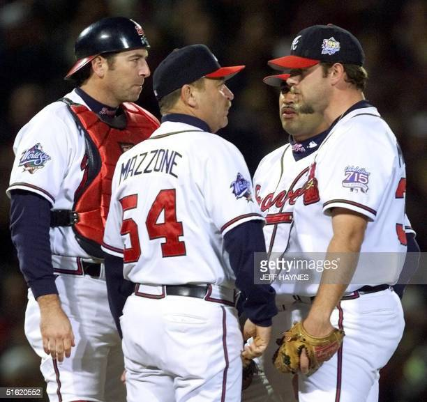 Starting pitcher Kevin Millwood of the Atlanta Braves in visted on the mound by pitching coach Leo Mazzone and catcher Greg Meyers in the 1st inning...