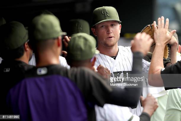 Starting pitcher Kyle Freeland of the Colorado Rockies is congratulated in the dugout after leaving the game in the ninth inning against the Chicago...