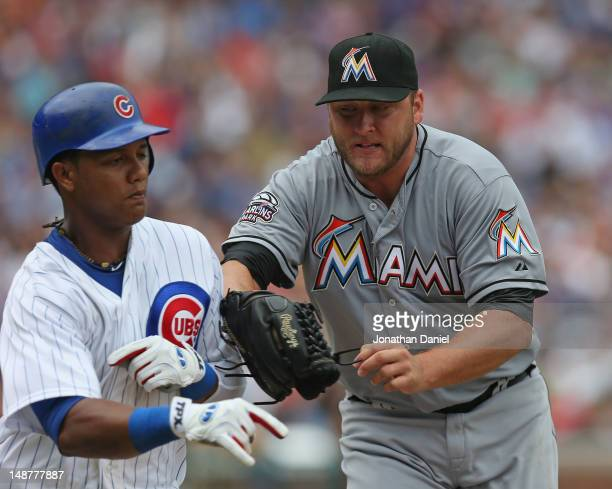 Starting pitcher Mark Buehrle of the Miami Marlins tages out Starlin Castro of the Chicago Cubs at Wrigley Field on July 19 2012 in Chicago Illinois
