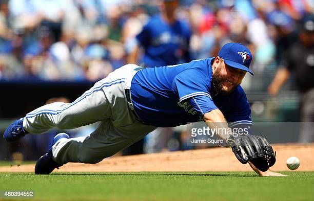 Starting pitcher Mark Buehrle of the Toronto Blue Jays dives for a ball hit back toward the mound during the game against the Kansas City Royals at...