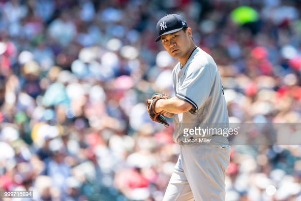Starting pitcher Masahiro Tanaka of the New York Yankees checks the runner on first during the fourth inning against the Cleveland Indians at...