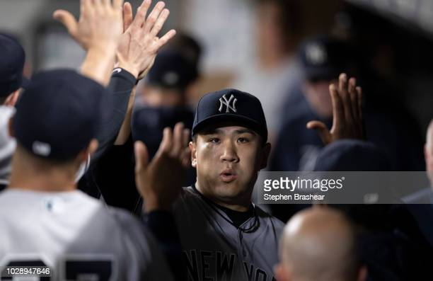 Starting pitcher Masahiro Tanaka of the New York Yankees is congratulated by teammates in the dugout after pitching the eighth inning of a game...