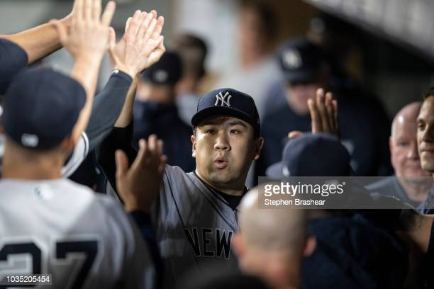 Starting pitcher Masahiro Tanaka of the New York Yankees is congratulated by teammates in the dugout during a game against the Seattle Mariners at...