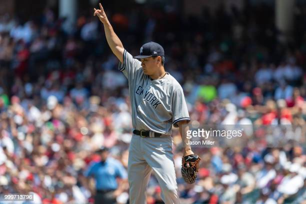 Starting pitcher Masahiro Tanaka of the New York Yankees signals to the outfield after Michael Brantley of the Cleveland Indians lined out to left...