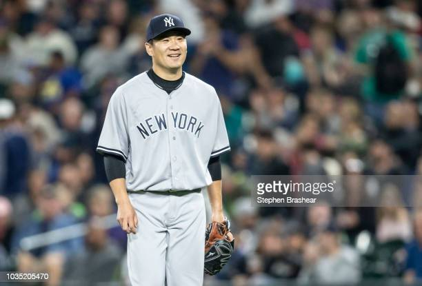 Starting pitcher Masahiro Tanaka of the New York Yankees smiles as he walks off the field during a game against the Seattle Mariners at Safeco Field...