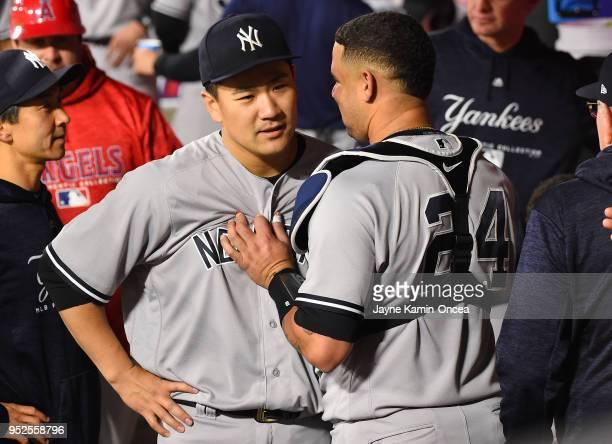 Starting pitcher Masahiro Tanaka of the New York Yankees talks with catcher Gary Sanchez of the New York Yankees in the dugout after the sixth inning...