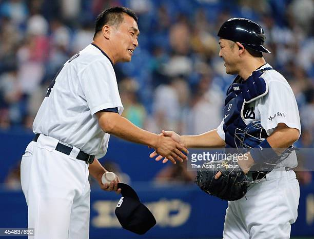 Starting pitcher Masahiro Yamamoto of Chunichi Dragons shakes hands with playing manager Motonobu Tanishige to celebrate the win after the Central...