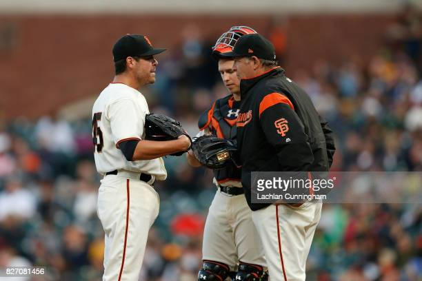 Starting pitcher Matt Moore of the San Francisco Giants talks to catcher Buster Posey and Pitching Coach Dave Righetti in the second inning against...